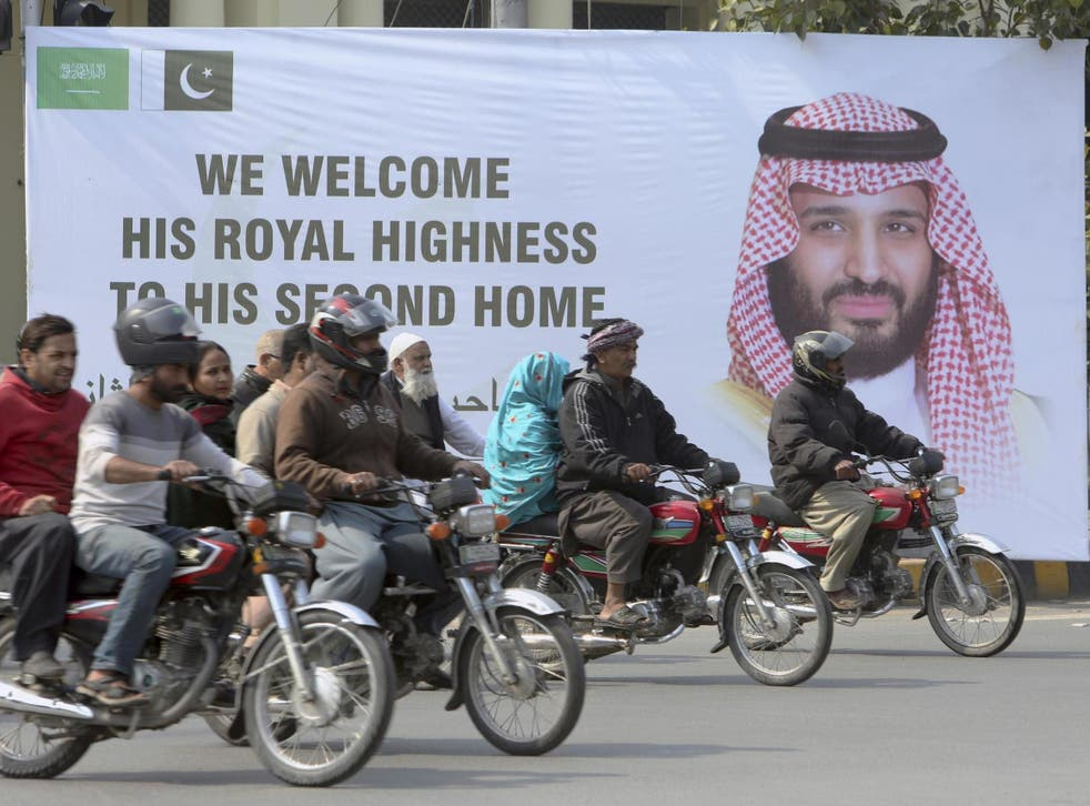 Pakistani motorcyclists pass by a banner welcoming Saudi Arabia's Crown Prince Mohammed bin Salman, displayed on the occasion of his visit in Lahore, Pakistan, on Saturday 16 February 2019.