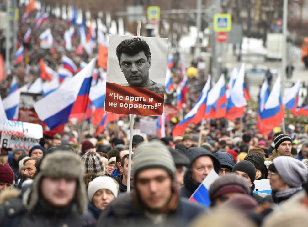 Demonstrators with Russian flags and a portrait of Boris Nemtsov, with words reading 'Do not lie, do not steal', march in Moscow, Russia