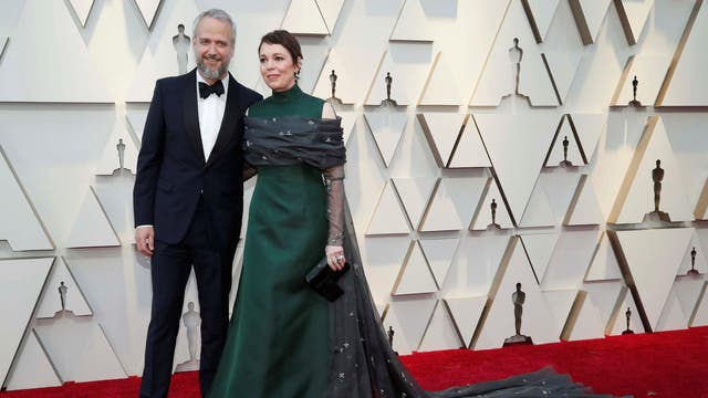 Olivia Colman looked regal in an emerald green high-neck dress by Prada with a long grey-coloured train.