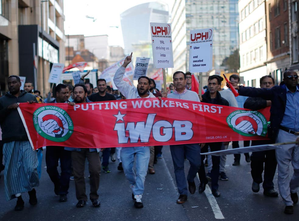 Drivers march in London with placards and banners from the IWGB