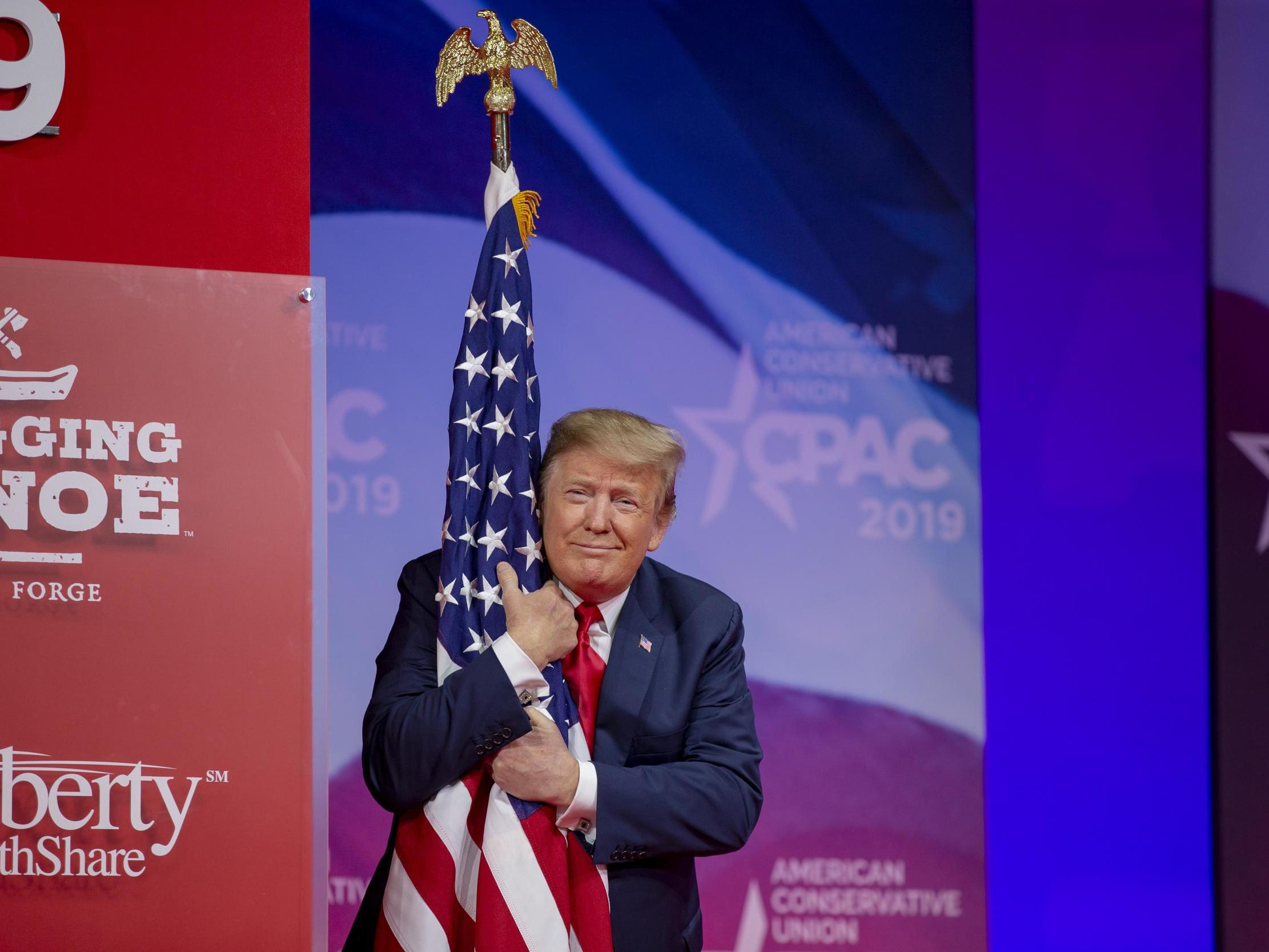 Trump goes off-script and hugs US flag in expletive-laden CPAC speech