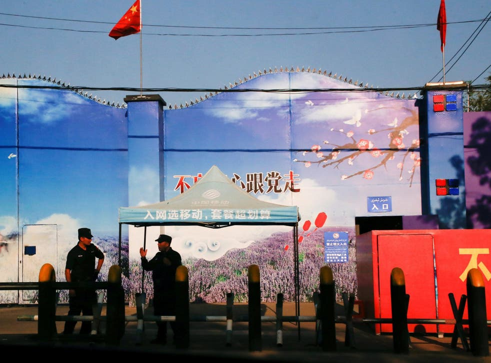 Security guards stand at the gates of what is officially known as a vocational skills education centre in Huocheng County in Xinjiang province