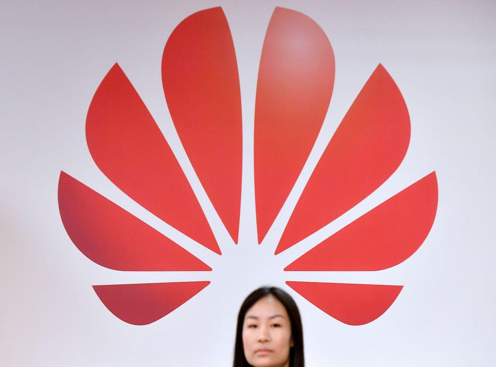 A woman walks past a logo at the entrance of the European Huawei Cyber Security Transparency Centre during its opening in Brussels on March 5, 2019