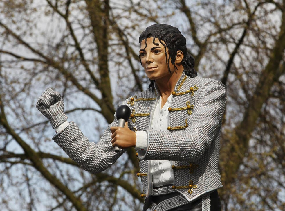 Former Fulham FC chairman Mohamed Al Fayed unveils a statue in tribute to Michael Jackson at the club's Craven Cottage stadium in April 2011.