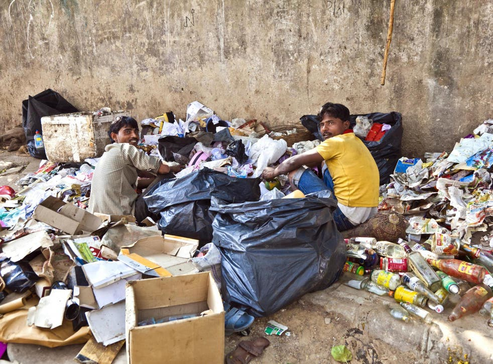 Workers checking rubbish for plastic and paper for waste separation in Delhi, India