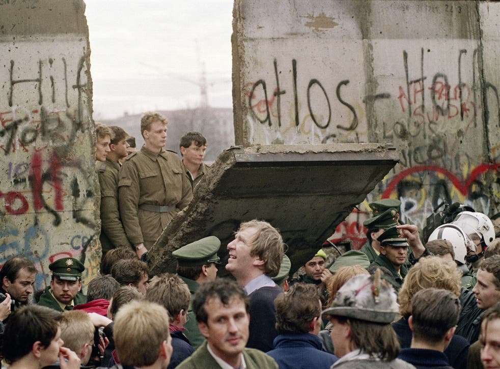 The day the wall came down: East German guards watch on as the concrete division comes tumbling down