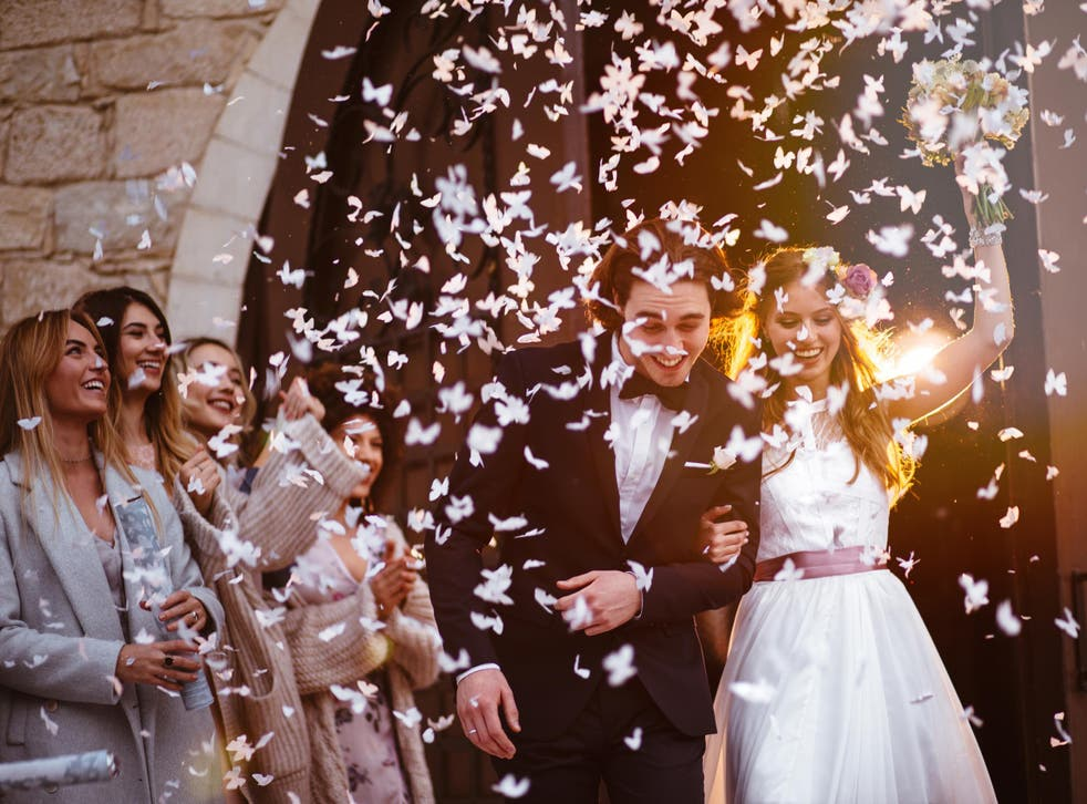 Newlywed husband and wife walking out of church and celebrating marriage with guests throwing confetti