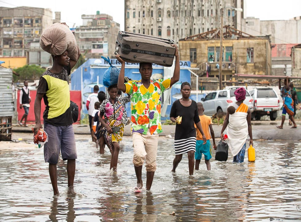 Residents of Beira in Mozambique carry their belongings through floodwater this week