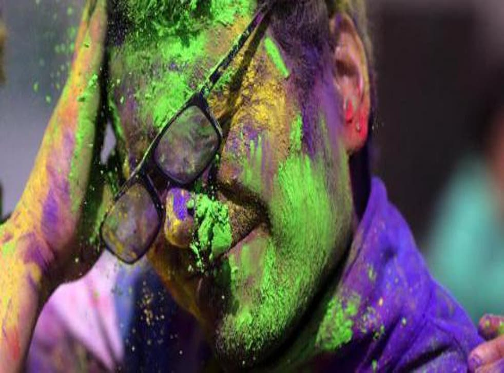 A young man is smeared in powdered colors by his friend as they take part in Holi festival celebrations at Durgiana Temple