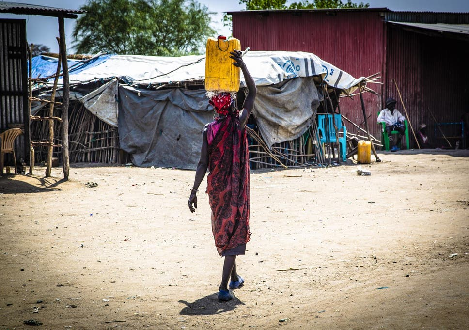 A woman walks to market carrying a jerry can of water (South Sudan)