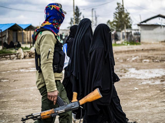 Foreign women living in al-Hol camp, which houses relatives of Isis members, walk under the supervision of a fighter of the Syrian Democratic Forces on 28 March 2019