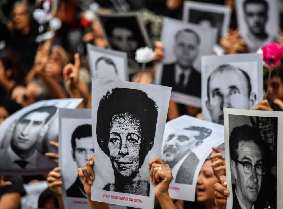 People hold pictures of those believed to have been killed or went missing during Brazil's 1964-1985 dictatorship, demonstrate on the 55th anniversary of the military coup.