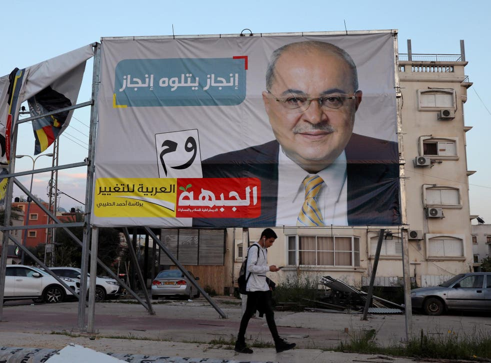 A youth walks past an Israeli election campaign banner depicting Ahmad Tibi, of the Hadash-Ta'al party in Taibe