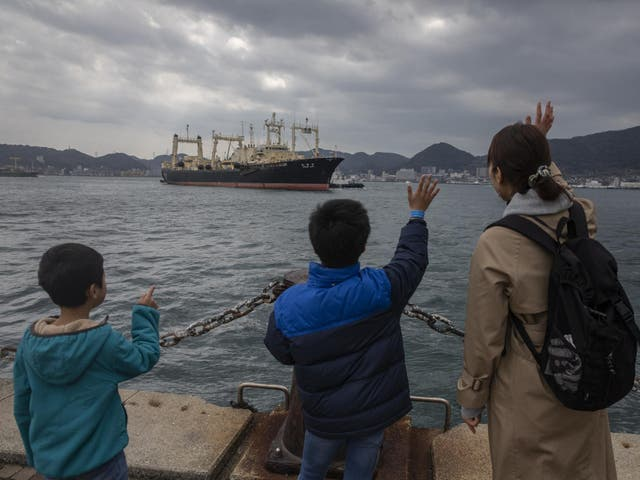 A family member waves at the Nisshin Maru crew as it returns to Shimonoseki on 31 March, 2019