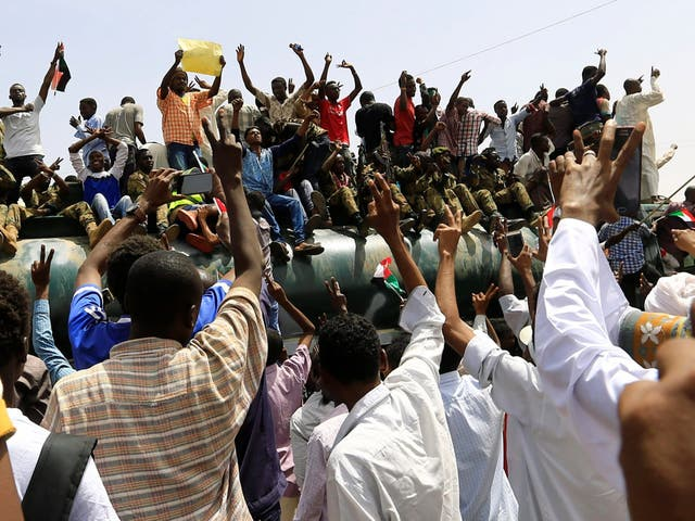 Sudanese demonstrators stand atop a military truck as they protest against the announcement of an army-led transitional council