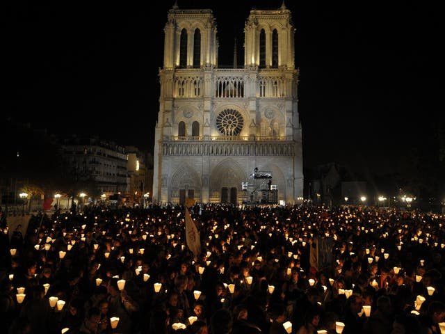 """Faithful hold candles during a """"Path of light"""" procession between Notre Dame Cathedral during the four-day visit in France of Pope Benedict XVI in 2008"""