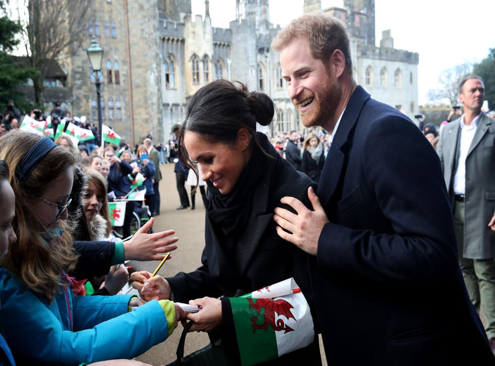 Prince Harry and Meghan Markle sign autographs and shake hands with children as they arrive to a walkabout at Cardiff Castle on January 18, 2018 in Cardiff, Wales