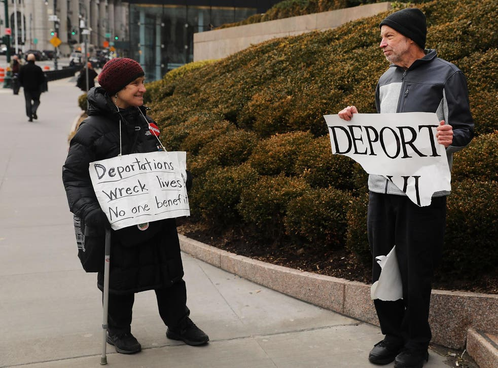 Pro Donald Trump protester (right) holds up sign calling for deportation in front of the Federal Building on 29 January 2018 New York City.