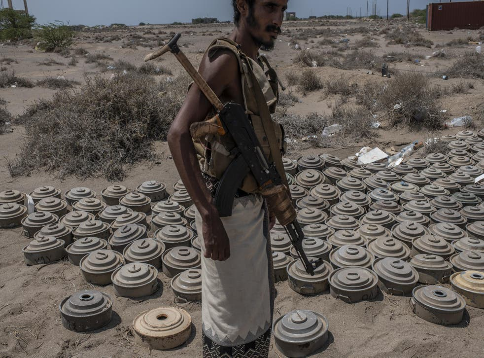 A fighter with the Tariq Salah Forces, a militia aligned with Yemen's Saudi-led coalition-backed government, shows Houthi rebel landmines the militia had recovered
