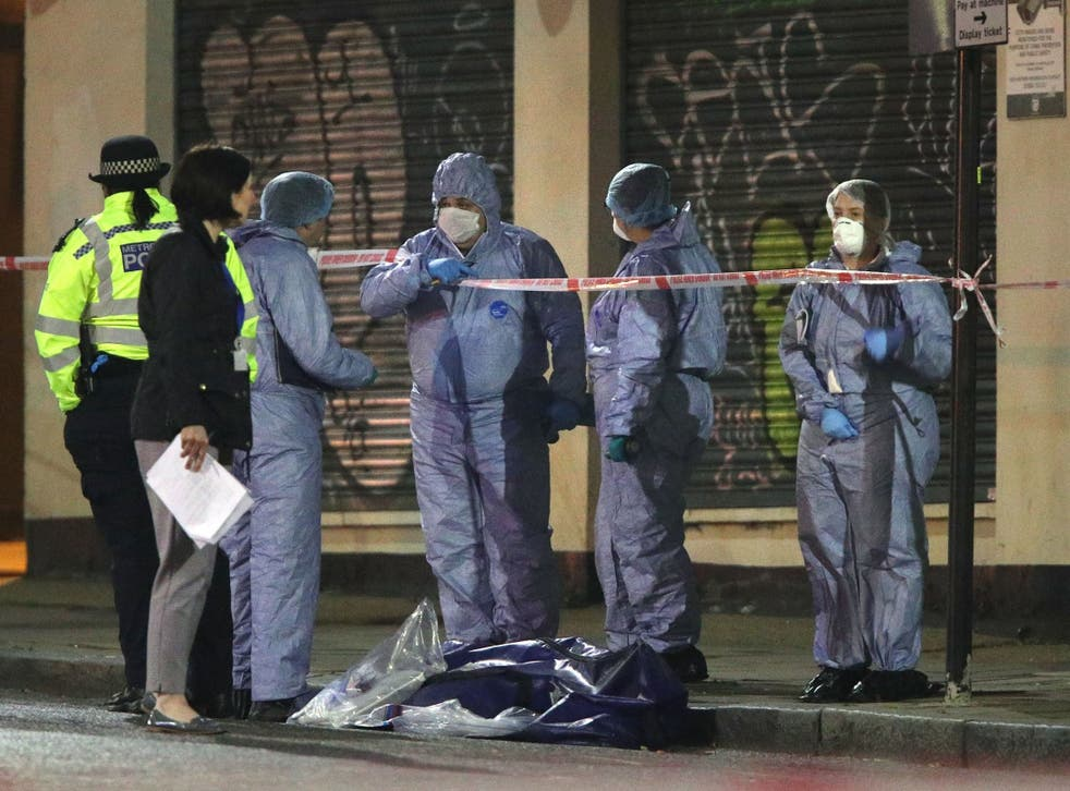 Forensic officers and police at the scene in Stoke Newington, northeast London, after a man was stabbed to death on 17 April