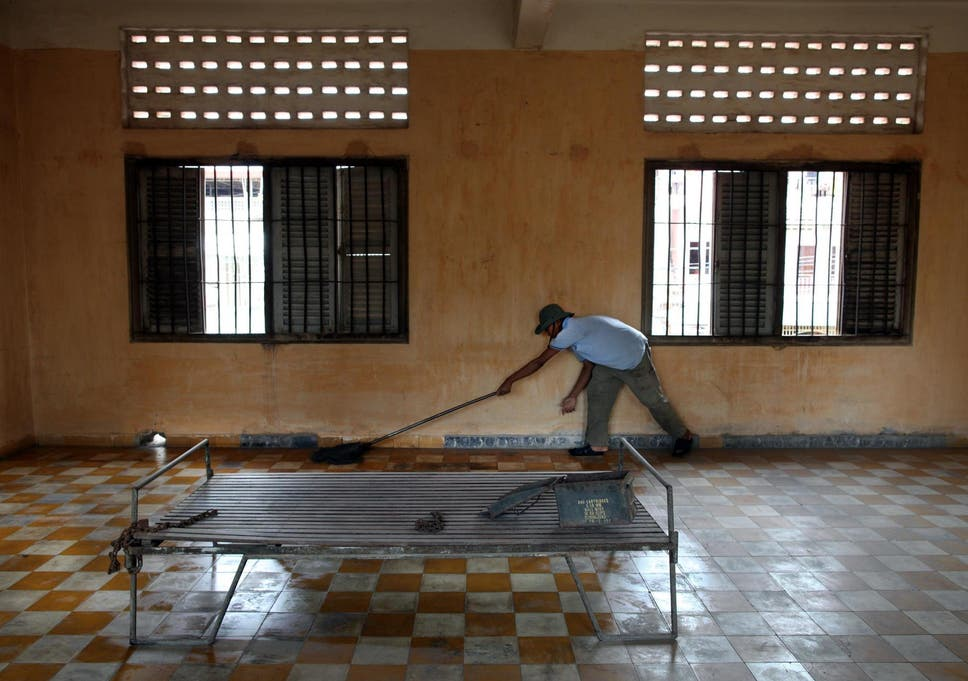 A worker cleans the floor inside the notorious S-21 prison known as Tuol Sleng, which has since been turned into a museum, where more than 15,000 people were executed during the Khmer Rouge regime