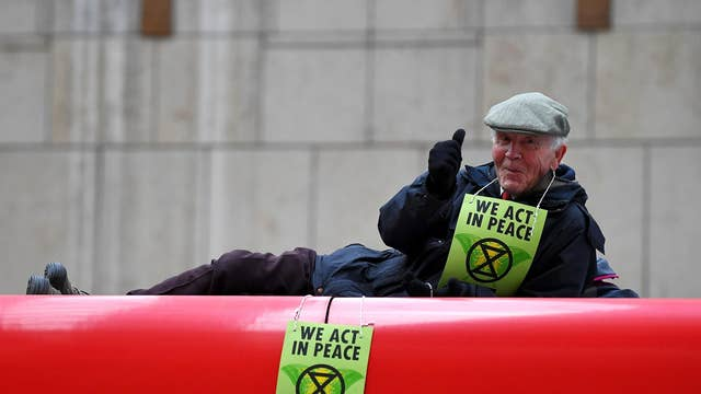 A protester gives a thumbs up as he stalls a DLR train at Canary Wharf station in London