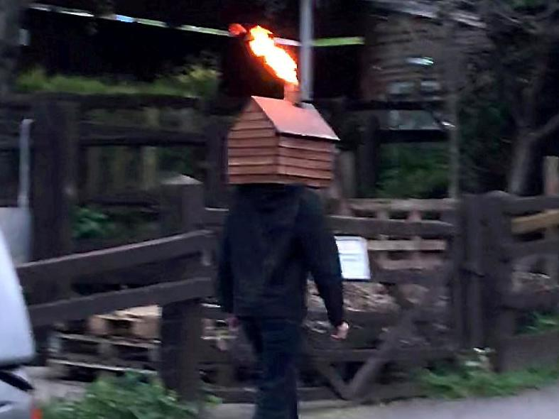 Man walks down street with disco shed on his head blasting fire from the chimney