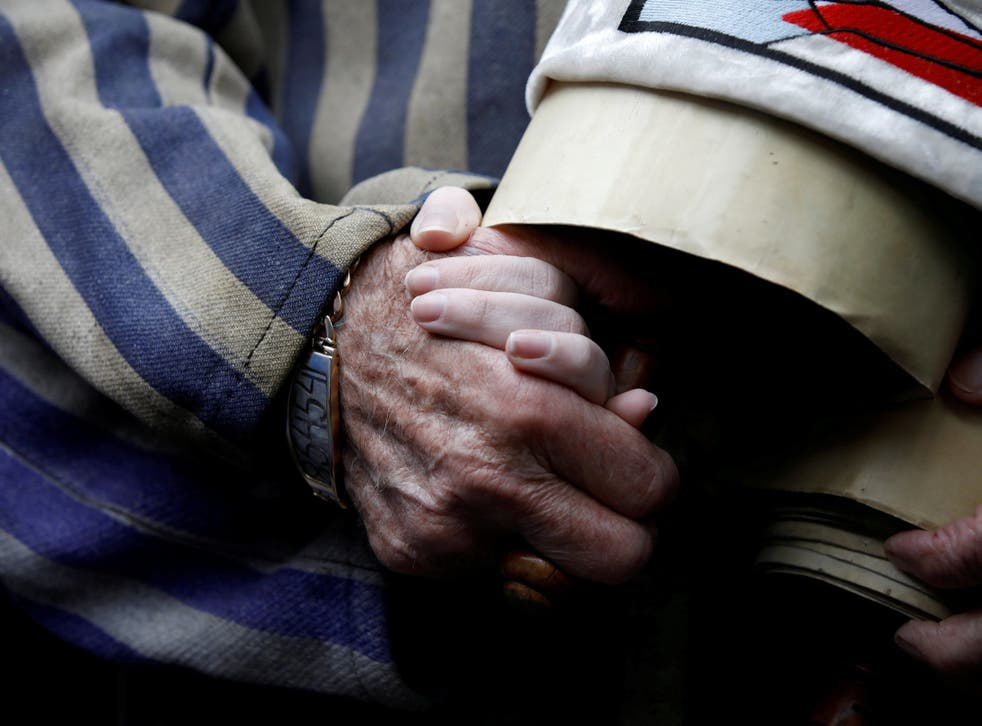 A Holocaust survivor holds his granddaughter's hand as he arrives to take part in this year's march in Poland