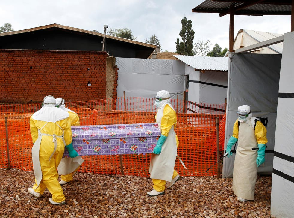 Health workers at a treatment centre in Butembo, DRC, carry the coffin of Kahambu Tulirwaho, who died of Ebola