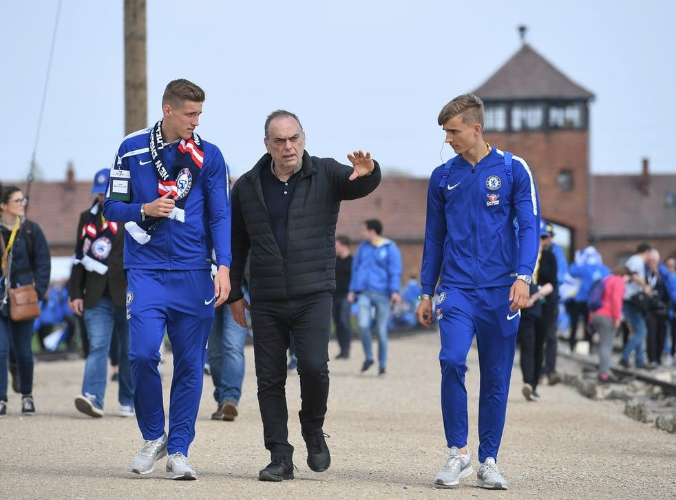 Avram Grant walks with two of Chelsea's academy players at Auschwitz