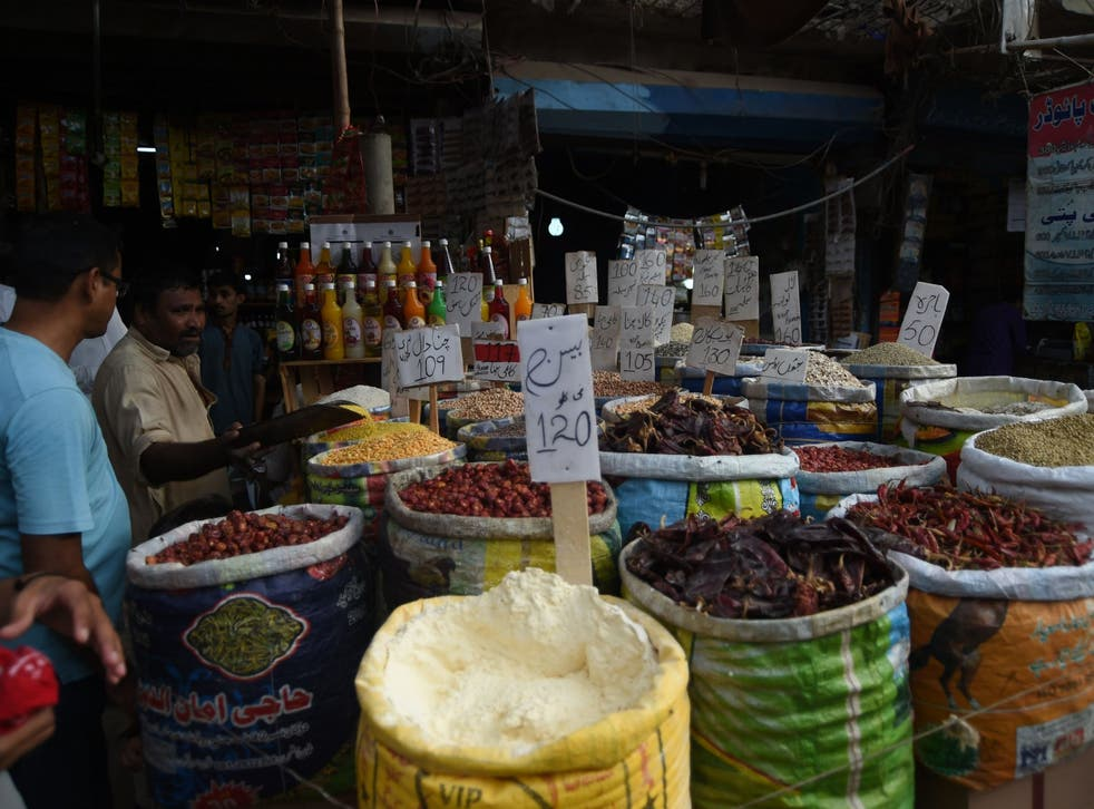 Pakistani customers buy grocery items at a market in Karachi on 10 May 2019. A government report has predicted that the country's growth rate was set to hit an eight-year low, leading to its 22nd bailout from the IMF.