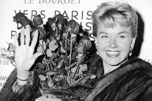 Doris Day is pictured in 1955 holding a bouquet of roses at Le Bourget Airport in Paris, France after flying in from London.
