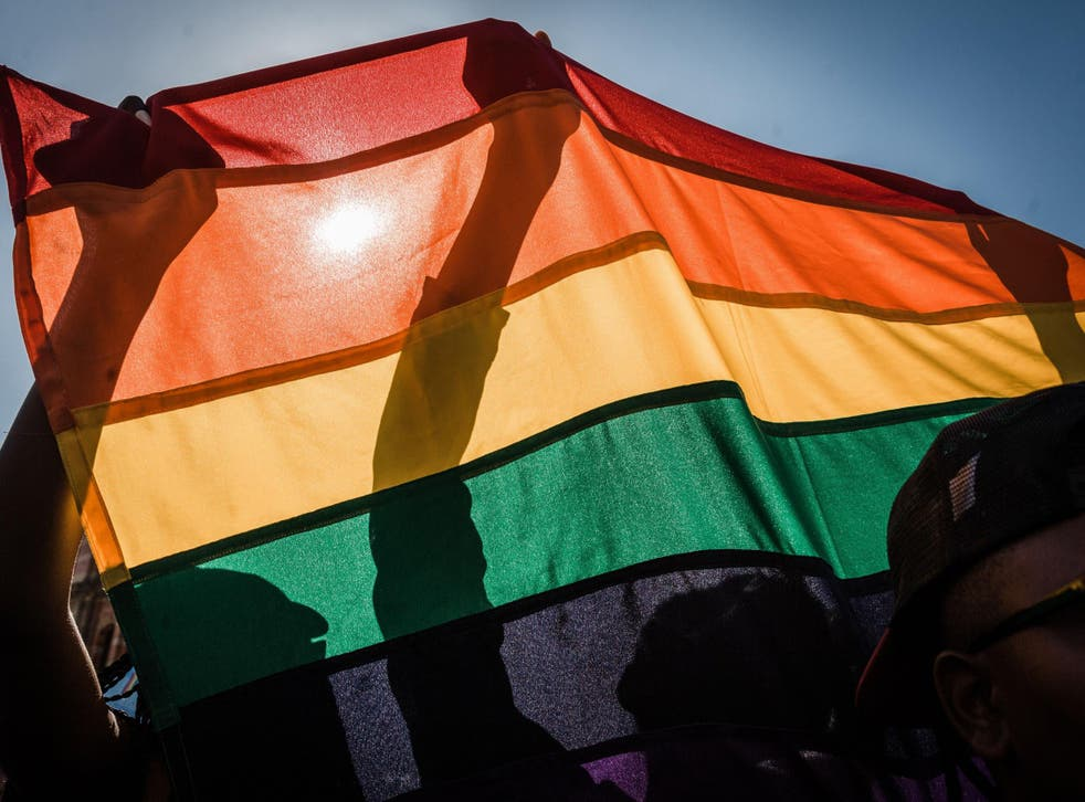 Pride activists fly an LGBT+ flag at a march in South Africa