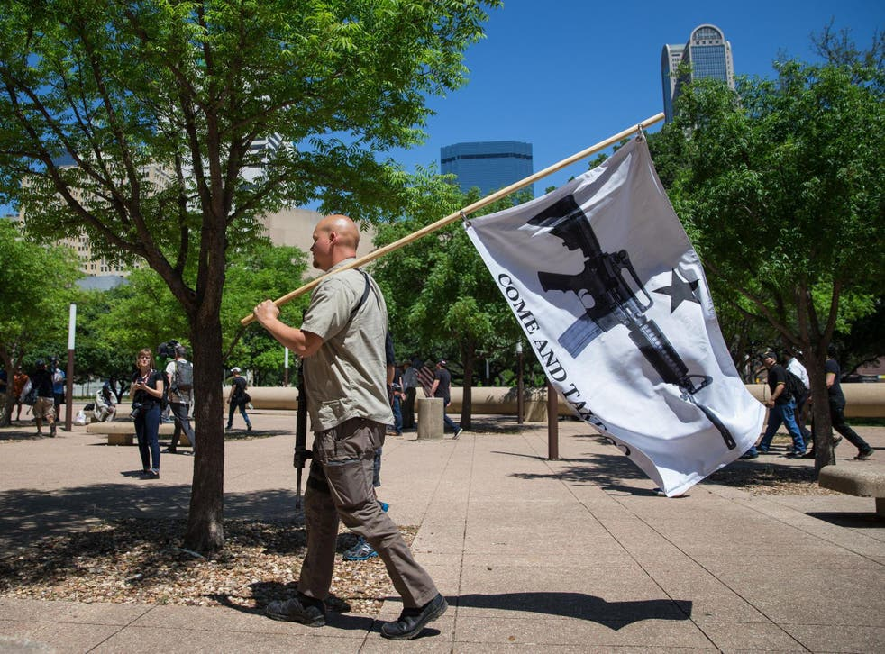 """Gun advocate in Texas holds """"come and take it"""" flag"""