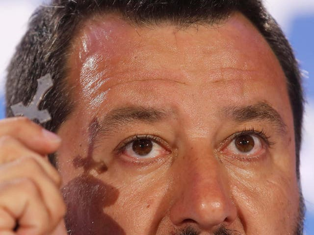 Matteo Salvini holds a crucifix as he talks to reporters during a press conference at the League headquarters in Milan on Monday
