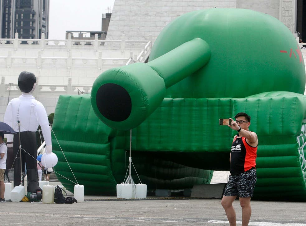 Taiwanese man takes a selfie with an inflatable tank installation in Taipei square