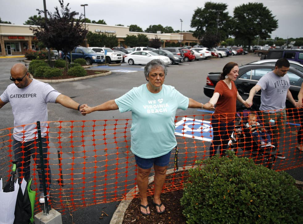 Lisa Dunaway, centre, of Virginia Beach, holds hands with other mourners during a vigil in response to a fatal shooting at a municipal building