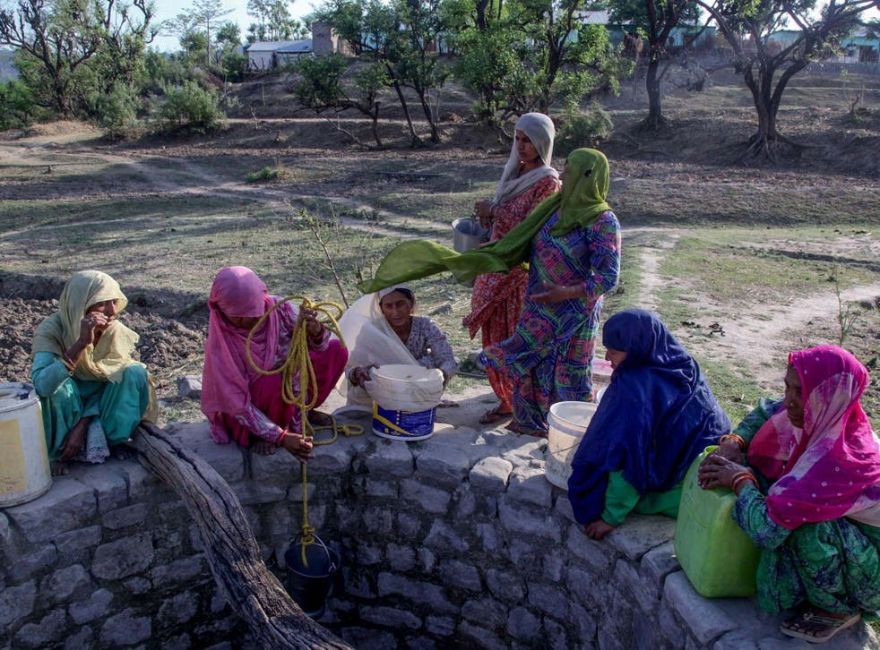 Indian villagers try to gather water from a well running dry in searing heat near Jammu