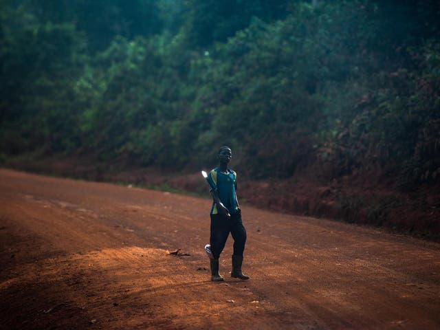 A boy holds a machete on his way to a farm
