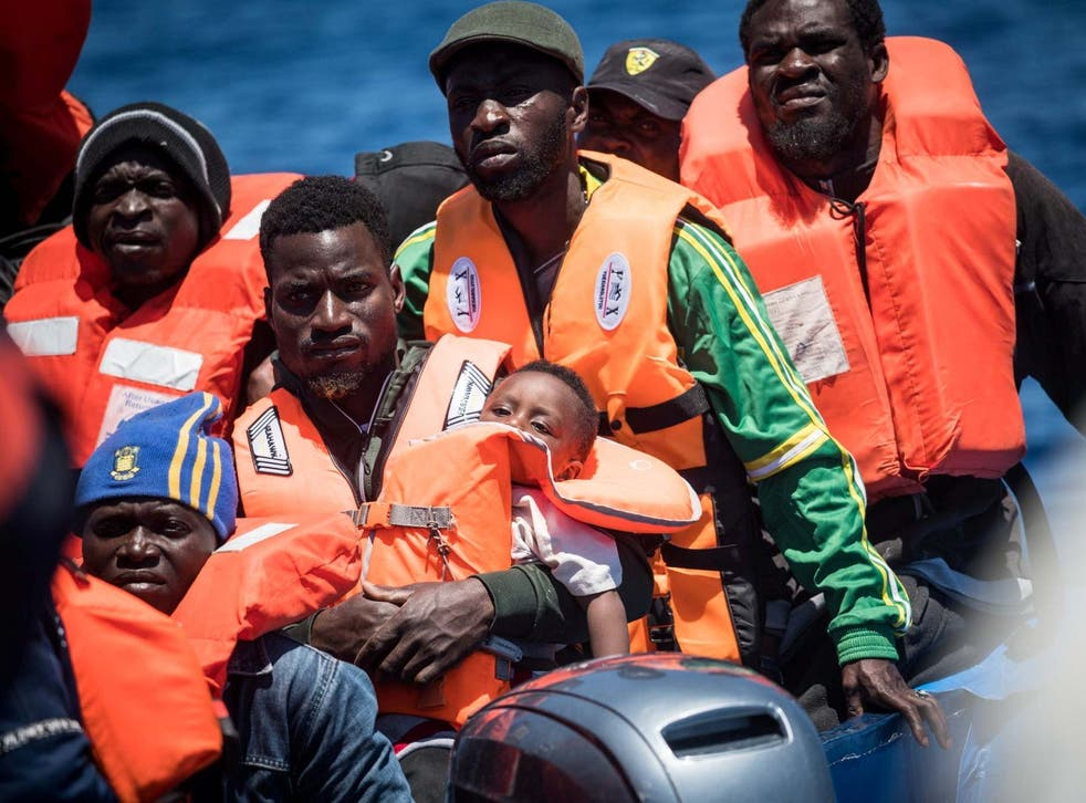 Refugees float on a dinghy before they are rescued off the coast of Lampedusa, Italy