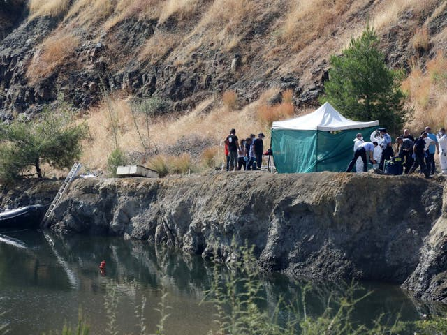 Cypriot police remove the remains of a girl, believed to be a six-year-old, from a lake near the village of Xiliatos