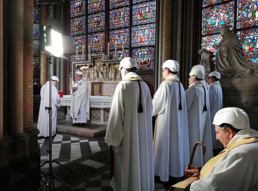 Clerics in hard hats attend a mass led by Michel Aupetit, Archbishop of Paris, in Notre Dame