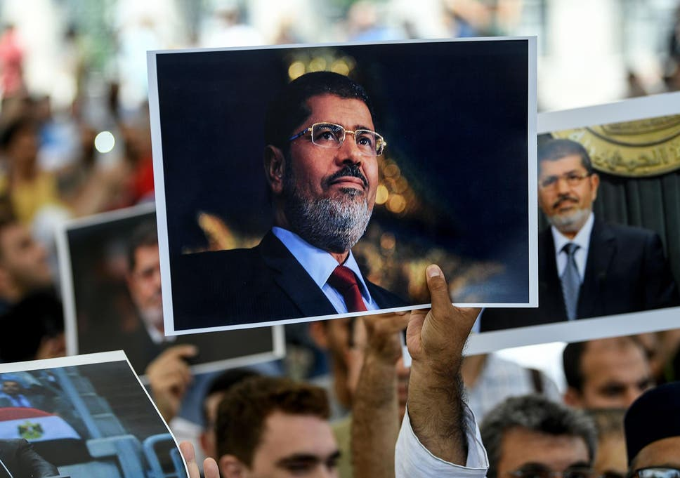 People hold pictures of Egyptian President Mohamed Morsi during a symbolic funeral ceremony on 18 June 2019 at Fatih mosque in Istanbul.