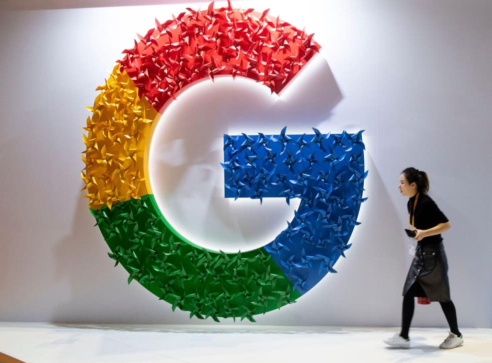 This picture taken on November 5, 2018 shows a woman passing a booth of Google at the first China International Import Expo (CIIE) in Shanghai