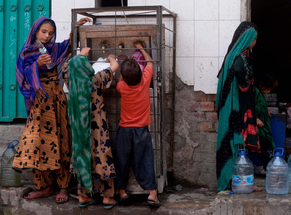 Afghan refugees fill water bottles near their makeshift houses in Lahore on 19 June 2019, ahead World Refugees Day on 20 June.
