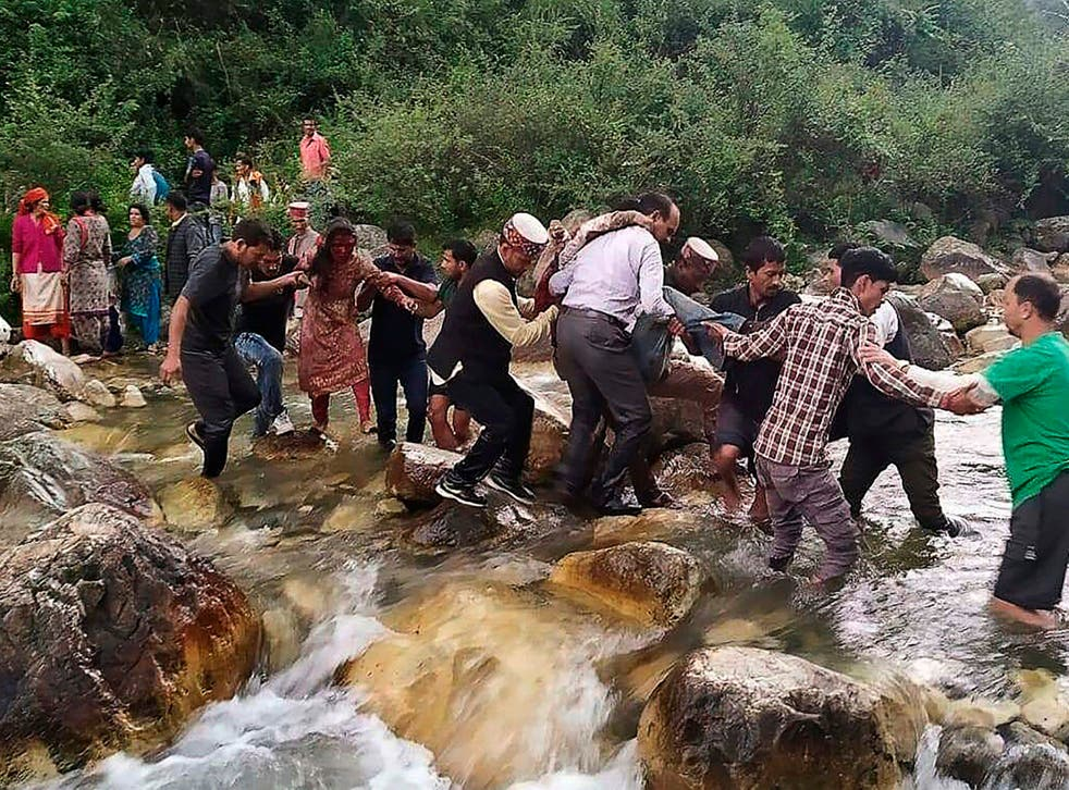 Local residents help accident survivors cross a river after a bus crash in the mountainous Kullu district of the Indian state of Himachal Pradesh