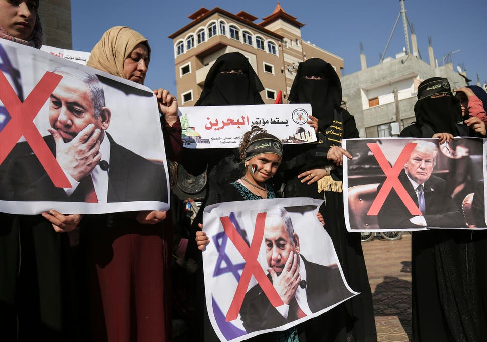 Palestinian female supporters of the Islamic Jihad carry posters of US President Donald Trump and Israeli Prime Minister Benjamin Netanyahu during a protest against the Bahrain economic workshop