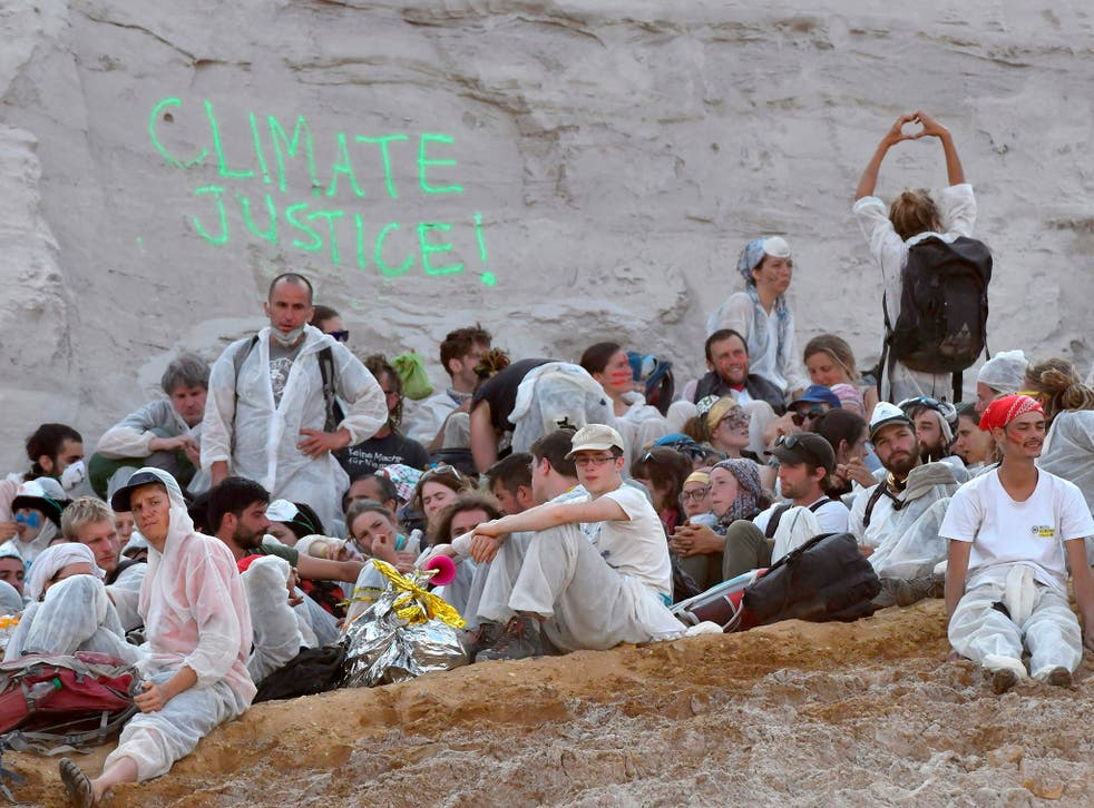 Climate activists sit on the ground after breaking through a police cordon and entering the Garzweiler coal mine in western Germany