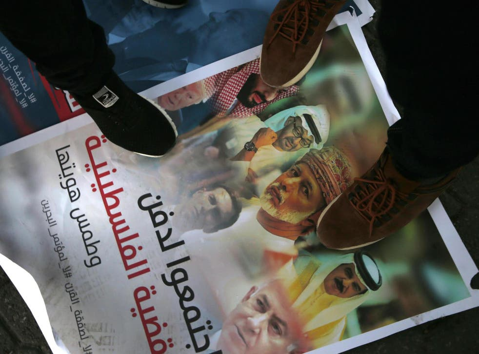 Palestinians step on a placard displaying pictures of Bahraini King Hamad al-Khalifa, Israeli Prime Minister Benjamin Netanyahu, US President Donald Trump and his son-in-law and adviser Jared Kushner, during a protest.