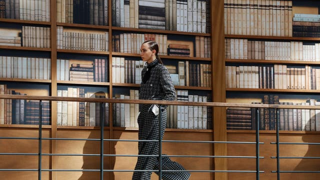 A model walks in a monochrome tweed suit with a pinned tie past a wall of bookshelves